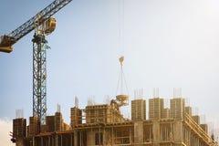 Costruendo in costruzione con una gru funzionante Fotografie Stock