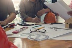 Costruisca il gruppo dell'ufficio di Architects che lavora e che discute la pianta della casa con i modelli ed alloggi il modello Fotografia Stock