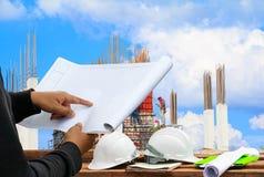 Costruisca il punto del dito sul modello di carta di piano nel cantiere del posto del tecnico della costruzione del controllo fotografie stock libere da diritti