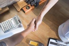 Costruisca il segno finito sul contratto di carta e stringa le mani immagine stock