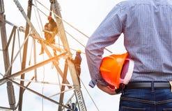 Costruisca la tenuta del casco di sicurezza giallo con gli elettricisti che lavorano alla torre della costruzione del pilone Fotografia Stock