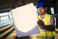 Costruisca lavorare al cantiere e la tenuta del modello fotografia stock