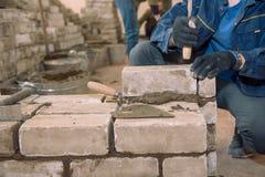 Costruisca una parete dei mattoni Gli studenti imparano porre i mattoni Mattoni del legame del cemento Cemento tamped spatola Cos fotografie stock libere da diritti