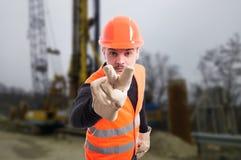 Costruttore attraente che fa il ` m. di I che vi guarda gesture fotografie stock