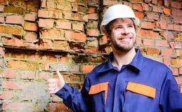 Costruttore bello barbuto del casco protettivo del tipo Fondo del muro di mattoni del cantiere del casco del costruttore Rottura  fotografia stock