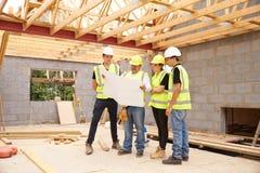 Costruttore On Building Site che esamina i piani con gli apprendisti immagini stock