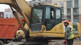Costruttore in casco arancio che fuma vicino all'escavatore funzionante al cantiere stock footage