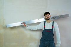Costruttore caucasico con il righello della costruzione sulla spalla nello spazio libero interno fotografie stock libere da diritti