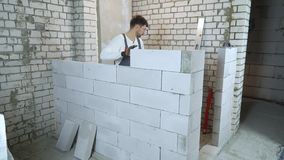 Costruttore caucasico nell'usura del lavoro che pone blocco e che lo controlla con la livella a bolla archivi video