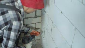 Costruttore che avvita in viti nella parete del blocco con il trapano elettrico video d archivio