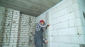 Costruttore che controlla le marcature sulla parete aerata del blocco in calcestruzzo con il righello della costruzione stock footage
