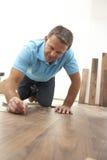 Costruttore che pone pavimentazione di legno Immagine Stock