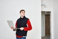 Costruttore con il computer portatile su oggetto Fotografie Stock