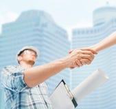 Costruttore con il modello che stringe la mano del partner Fotografia Stock