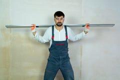 Costruttore con il righello della costruzione sulle sue spalle con la parete vuota su fondo fotografia stock