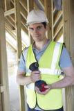 Costruttore On Construction Site che tiene trapano senza cordone Immagine Stock Libera da Diritti