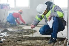 Costruttore del caporeparto che ispeziona i lavori di costruzione concreti in appartamento fotografie stock libere da diritti