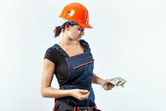 Costruttore della giovane donna nelle banconote di una tenuta del casco Fotografia Stock Libera da Diritti