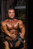 Costruttore di corpo maschio che fa esercizio pesante per la parte posteriore Fotografia Stock