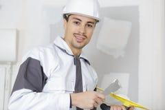 Costruttore felice in elmetto protettivo che intonaca parete Fotografia Stock