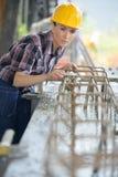 Costruttore femminile che lavora con i tubi alla fabbrica Immagine Stock Libera da Diritti