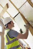 Costruttore Fitting Insulation Boards nel tetto di nuova casa Fotografia Stock