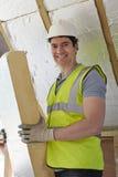 Costruttore Fitting Insulation Boards nel tetto di nuova casa Immagini Stock