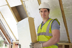 Costruttore Fitting Insulation Boards nel tetto di nuova casa Fotografia Stock Libera da Diritti