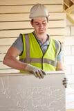 Costruttore Fitting Insulation Boards nel tetto di nuova casa immagini stock libere da diritti