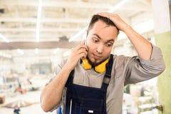 Costruttore imbarazzato che rivolge al telefono dal cantiere fotografie stock libere da diritti