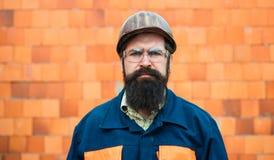 Costruttore Lavoratore meccanico del ritratto Uomo barbuto in vestito con il casco della costruzione Ritratto dell'ingegnere bell immagini stock