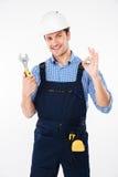 Costruttore nella chiave della tenuta del casco e nel segno giusto di rappresentazione Immagini Stock