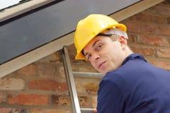 Costruttore o roofer su una scaletta immagini stock libere da diritti