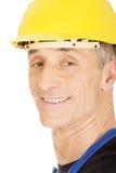 Costruttore sorridente con un casco di sicurezza Fotografie Stock Libere da Diritti