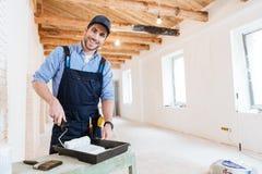 Costruttore sorridente facendo uso del rullo di pittura all'interno immagine stock