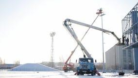 Costruttore su una piattaforma dell'ascensore ad un cantiere Uomini sul lavoro impalcatura di montaggio del muratore sul cantiere stock footage