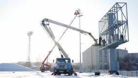 Costruttore su una piattaforma dell'ascensore ad un cantiere Uomini sul lavoro impalcatura di montaggio del muratore sul cantiere video d archivio