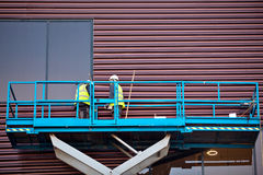 Costruttore su una piattaforma dell'ascensore di forbici ad un cantiere Fotografia Stock Libera da Diritti