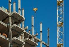 Costruttori con la gru che costruisce casa multistorey fotografia stock