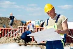 Costruttori dell'assistente tecnico al cantiere con la cambiale immagine stock