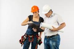 Costruttori in elmetto protettivo o in casco che discutono i modelli con la compressa immagine stock libera da diritti