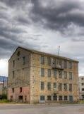 Costruzione abbandonata della fabbrica sotto il cielo nuvoloso Immagine Stock Libera da Diritti