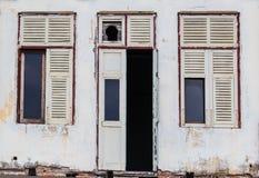 Costruzione bianca abbandonata della facciata con la porta e le finestre di legno rovinate Fotografia Stock Libera da Diritti