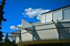 Costruzione bianca moderna e nelle nuvole dell'en del cielo blu del fondo Immagini Stock