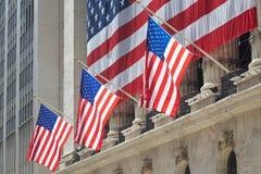 Costruzione con con tre bandiere degli Stati Uniti, distretto finanziario di borsa valori di Wall Street a New York Immagine Stock Libera da Diritti