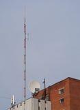 Costruzione con le antenne ed il riflettore parabolico Fotografia Stock Libera da Diritti