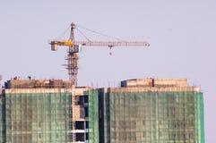 Costruzione in costruzione con una gru sulla cima e sulle reti di sicurezza Fotografie Stock