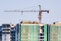 Costruzione in costruzione con una gru sulla cima e sulle reti di sicurezza Immagini Stock Libere da Diritti