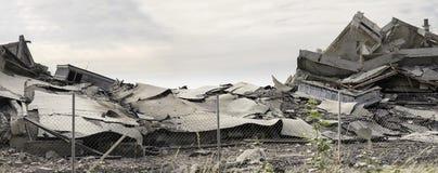 Costruzione concreta industriale destructed dal colpo Scena di disastro in pieno di detriti, di polvere e di costruzioni schianta immagini stock