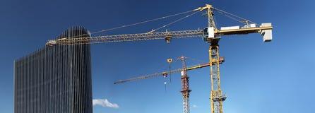 Costruzione in costruzione del sito con il grattacielo di vetro e della gru Immagini Stock